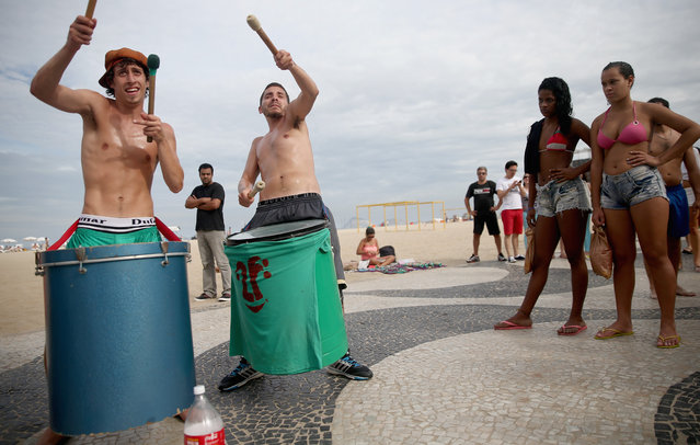 Argentine drummers from the band La Fantastica perform as Brazilians (R) watch on Copacabana Beach on July 7, 2014 in Rio de Janeiro, Brazil. Brazil plays Germany tomorrow in the first semi-final match of the 2014 FIFA World Cup while Argentina faces the Netherlands Wednesday. (Photo by Mario Tama/Getty Images)