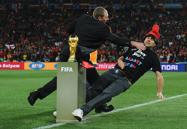 A pitch invader is wrestled away from the World Cup Trophy by security, prior to the 2010 FIFA World Cup South Africa Final match between Netherlands and Spain at Soccer City Stadium on July 11, 2010 in Johannesburg, South Africa. (Photo by Laurence Griffiths/Getty Images)