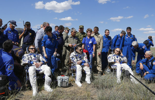 The International Space Station crew, from left, Britain's Tim Peake, Russia's Yuri Malenchenko and Tim Kopra of US, surrounded by ground personnel, rest shortly after landing near the town of Dzhezkazgan, Kazakhstan, Saturday, June 18, 2016. (Photo by Shamil Zhumatov/Pool Photo via AP Photo)