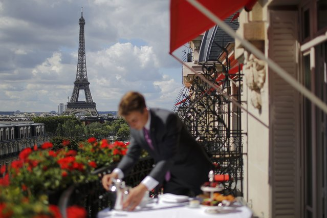 An employee prepares breakfast in front of the Eiffel tower at the Parisian luxury hotel Le Plaza Athenee, France July 30, 2015. Nowhere in the world has more accommodation available on Airbnb than Paris. Now the home-sharing website that has transformed budget travel to the French capital is giving its super-deluxe hotels a fright too. (Photo by Stephane Mahe/Reuters)