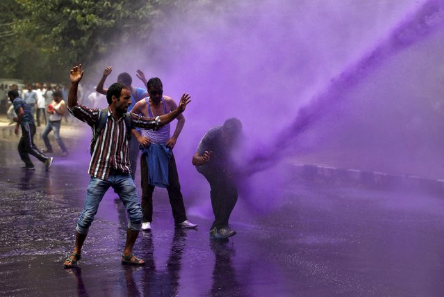 Government employees are hit by dyed water from a water cannon used by Indian police to disperse protesters during a demonstration in Srinagar, August 10, 2015. Indian police on Monday detained dozens of protesting government employees in Srinagar who were demanding their long pending arrears and a regularisation of temporary jobs, according to protesters. (Photo by Danish Ismail/Reuters)
