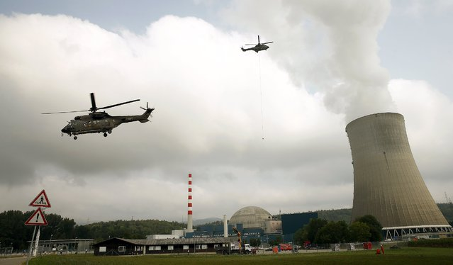 Swiss air force helicopters fly during an exercise over the Swiss nuclear power plant Goesgen near the town of Daeniken west of Zurich August 11, 2015. The Swiss Federal Nuclear Safety Inspectorate (ENSI) tested, with the co-operation of the Swiss air force and the power plant operators, the transport of technical emergency equipment by air. (Photo by Arnd Wiegmann/Reuters)