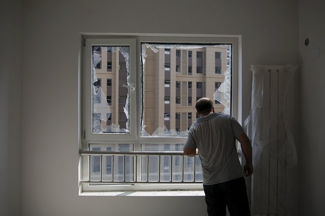 A man looks out from inside a damaged residential building near the site of the explosions at the Binhai new district, Tianjin, August 13, 2015. (Photo by Damir Sagolj/Reuters)