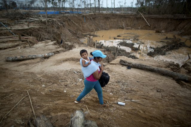 People leave a camp after a Peruvian police operation to destroy illegal gold mining camps in La Pampa, in the southern Amazon region of Madre de Dios, Peru  August 11, 2015. Picture taken August 11, 2015. (Photo by Sebastian Castaneda/Reuters)