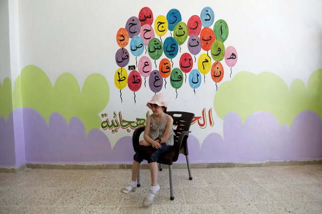"""A student sits in front of a wall decorated with Arabic alphabet inside the """"Syria, The Hope"""" school on the outskirts of the rebel-controlled area of Maaret al-Numan town, in Idlib province, Syria June 1, 2016. (Photo by Khalil Ashawi/Reuters)"""