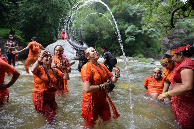 Hindu devotees bathe in the Bagmati River on their way to the Pashupatinath Temple to offer prayers to Lord Shiva, Hindu god of destruction during Shravan festivities in Sundarijal, on the outskirts of Kathmandu on July 21, 2014. According to the Nepali calendar, Shravan is considered the holiest month of the year with each Monday of the month known as Shravan Somvar when worshippers offer prayers for a happy and prosperous life. (Photo by Prakash Mathema/AFP Photo)