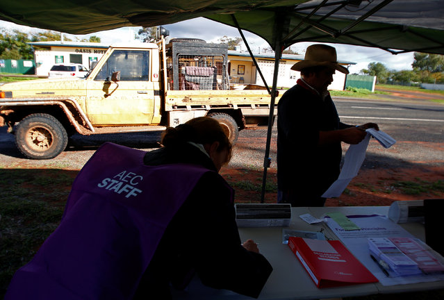 Farmer Darrell Peirpoint holds his Australian Senate ballot paper as assistant Heather McInerney prepares an official form at the remote voting station in the western New South Wales outback town of Enngonia, Australia, June 22, 2016. (Photo by David Gray/Reuters)