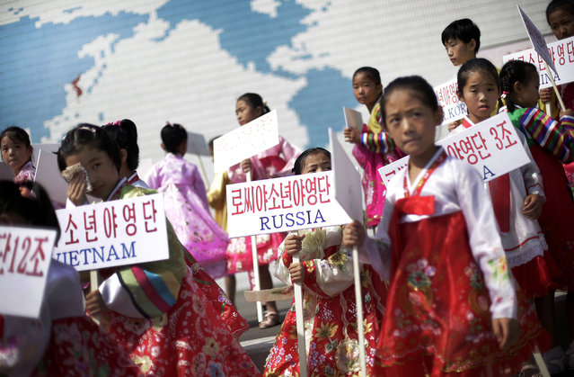 Young North Korean girls hold up signboards with the names of participating countries during an opening ceremony at the Songdowon International Children's Camp, Tuesday, July 29, 2014, in Wonsan, North Korea. The camp, which has been operating for nearly 30 years, was originally intended mainly to deepen relations with friendly countries in the Communist or non-aligned world. But officials say they are willing to accept youth from anywhere – even the United States. (Photo by Wong Maye-E/AP Photo)