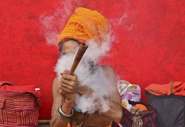 A Sadhu or a Hindu holyman smokes a pipe before registering for the annual pilgrimage to the Amarnath cave shrine, at a base camp in Jammu, June 30, 2016. (Photo by Mukesh Gupta/Reuters)