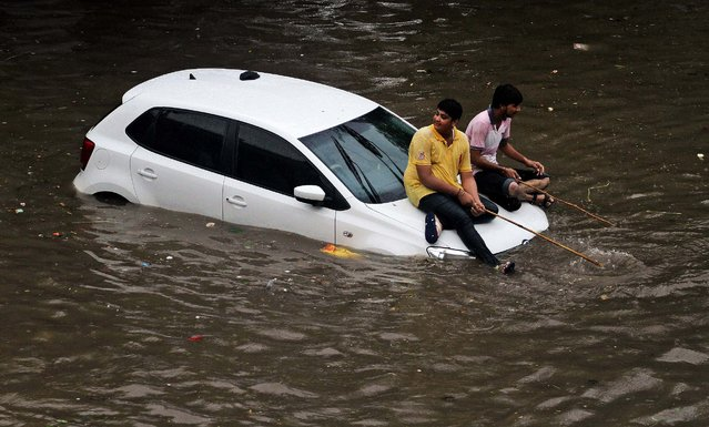Boys sit and play with sticks on a partially submerged car in a waterlogged street in Ahmadabad, India, on Jule 30, 2014. Rail and air traffic in several areas of Gujarat state were disrupted due to heavy rainfall, according to news reports. (Photo by Ajit Solanki/Associated Press)