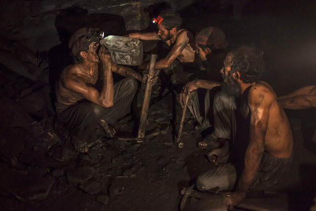 Miners take a break to drink water inside a coal mine in Choa Saidan Shah, Punjab province, April 29, 2014. (Photo by Sara Farid/Reuters)