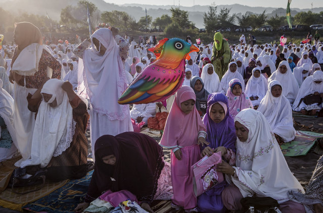 "Indonesian muslim women attend Eid Al-Fitr prayer on ""sea of sands"" at Parangkusumo beach on July 6, 2016 in Yogyakarta, Indonesia. Eid Al-Fitr marks the end of Ramadan, during which Muslims in countries around the world spend time with family, offer gifts and often give to charity. (Photo by Ulet Ifansasti/Getty Images)"