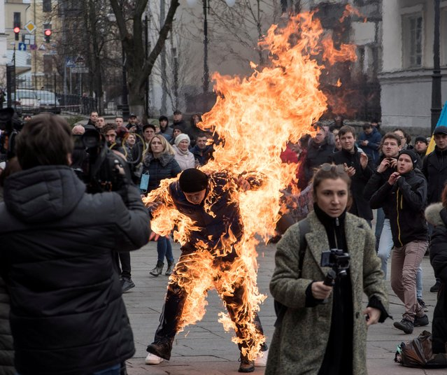 A man sets himself on fire during protest rallies in front of the presidential office in Kiev, Ukraine on February 26, 2020. The man, who called himself Oleksandr Burlakov, said subsequently that his motive was to draw the attention of the authorities to his plight, related to the ownership of the land parcel. (Photo by Ihor Behus/Reuters)
