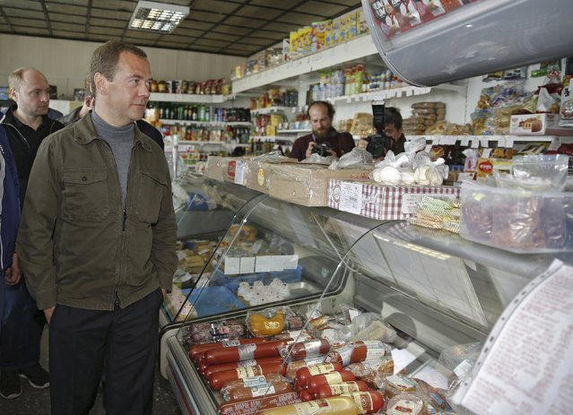 """Russia's Prime Minister Dmitry Medvedev inspects a grocery during his visit to Iturup Island, one of four islands known as the Southern Kurils in Russia and the Northern Territories in Japan, August 22, 2015. Medvedev visited the island on Saturday to attend the all-Russian youth educational forum """"Iturup"""", according to local media. (Photo by Dmitry Astakhov/Reuters/RIA Novosti)"""