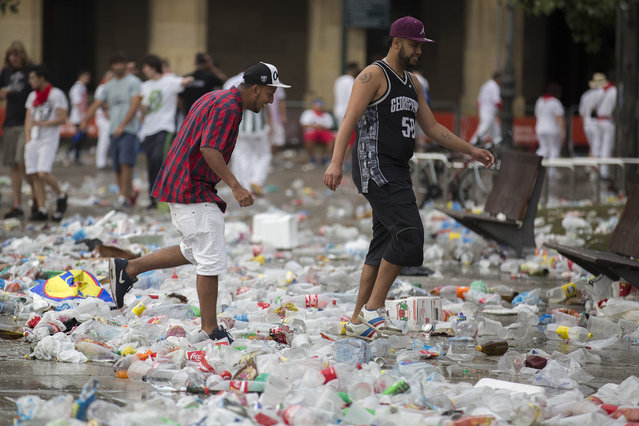 Foreign revellers in the Fiesta de San FermÌn walk through a sea of discarded plastic bottles, beer cans and rubish after a long, hard night's partying in Pamplona, northern Spain, July 10, 2016. (Photo by Jim Hollander/EPA)