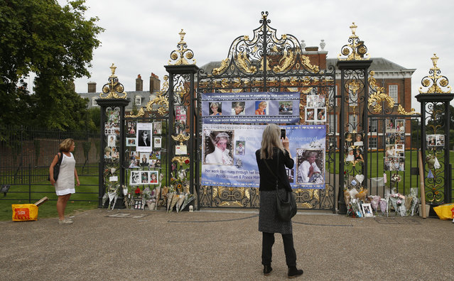 Tourists look at tributes and memorabilia for the late Diana, Princess of Wales outside Kensington Palace in London, Tuesday, August 29, 2017. The tributes are placed on one of the ornamental gates at the palace ahead of the 20th anniversary of Princess Diana's death, in a car crash in Paris Aug. 31, 1997. (Photo by Alastair Grant/AP Photo)