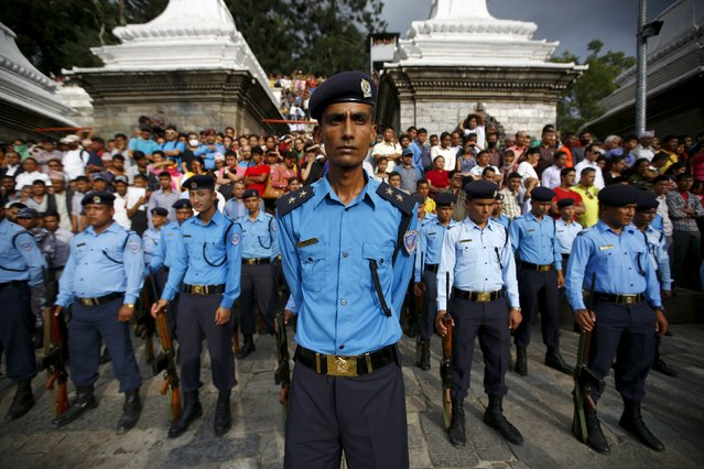 Nepali police stand during a cremation ceremony of Senior Superintendent of Police (SSP) Laxman Neupane, who was killed in Monday's protest, at Tikapur in Kailali district, Nepal August 25, 2015. (Photo by Navesh Chitrakar/Reuters)