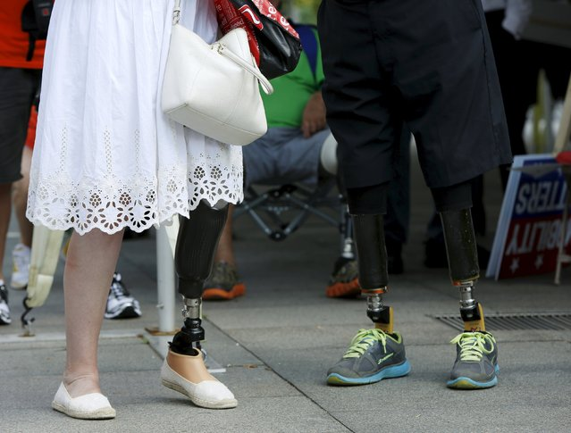 A man (R) and a woman chat during a protest held by the Amputee Coalition and the American Orthotic & Prosthetic Association in front of the Department of Health and Human Services in Washington, August 26, 2015. The group was protesting their concern over a Medicare rule proposal that would significantly impact care for two million amputees. (Photo by Gary Cameron/Reuters)