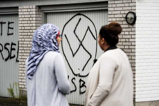 "Women look at a swastika, in front of the Red Cross asylum center in Lyngbygaard, in Trustrup in the west of Denmark August 27, 2015. The asylum center was vandalized by unidentified men, who drew Nazi symbols and wrote a message reading ""first warning"", on Wednesday night. A vehicle was also set on fire outside the center. (Photo by Bo Amstrup/Reuters/Scanpix Denmark)"