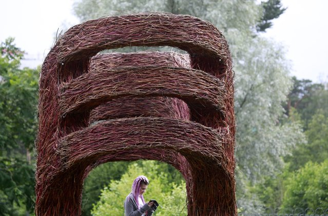 """A visitor is seen behind the art installation """"Hugs"""" by Belorussian designers Vasily Timashov and Polina Pirogova during the open air exhibition Art Islands-2016 in a park in Minsk, Belarus, 17 July 2016. The exhibition is on display until 31 August. (Photo by Tatyana Zenkovich/EPA)"""
