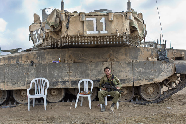 An Israeli soldier sits next to a Merkava tank in a staging area in southern Israel, along the border with the Gaza Strip, August 19, 2014. The Israeli military said three rockets had been fired from the Gaza Strip into southern Israel despite a ceasefire. (Photo by Jim Hollander/EPA)