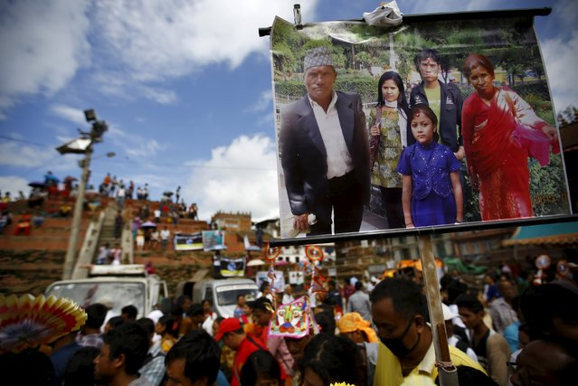 "A portrait of a family who died during the massive earthquake in April is carried by a family member during a parade to mark the Gaijatra festival, also known as ""cow festival"", in Kathmandu, Nepal August 30, 2015. (Photo by Navesh Chitrakar/Reuters)"
