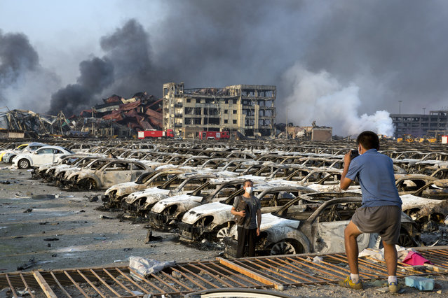 In this photo taken Thursday, August 13, 2015, a man takes photo for another near charred remains of new cars at a parking lot near the site of a warehouse explosion in northeastern China's Tianjin municipality.  People recently punished in China's campaign against online rumors include those who circulated an inflated death toll in the Tianjin blasts and who alleged a man committed suicide because of the country's stock market woes, state media reported Monday, Augus 31, 2015.(Photo by Ng Han Guan/AP Photo)