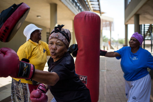 "77 year-old Gladys Ngwenya (C) and 79 year-old Constance Ngubane (R) take part in a ""Boxing Gogos"" (Grannies) training session hosted by the A Team Gym in Cosmo City in Johannesburg on September 19, 2017. (Photo by Gulshan Khan/AFP Photo)"