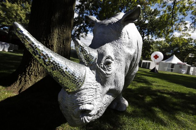 A rhinoceros sculpture with mirror-encrusted horns sits adjacent to a medical tent at the Electric Zoo music festival venue on New York's Randall's Island, Friday, August 29, 2014. (Photo by Jason DeCrow/AP Photo)