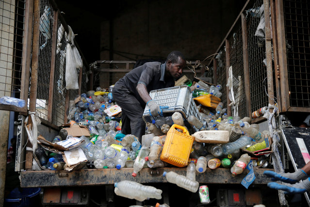 A man moves waste collected from homes from the back of a truck at the Wecycler waste recycling centre in Ebutte meta district in Lagos, Nigeria July 28, 2016. (Photo by Akintunde Akinleye/Reuters)