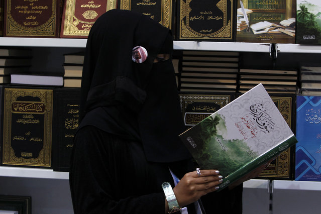 A veiled woman wearing a badge with a portrait of Saudi King Abdullah browses a book at the Riyadh International Book Fair, March 6, 2012. (Photo by Fahad Shadeed/Reuters)