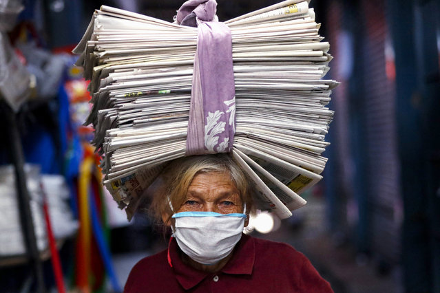 """Guillermina de Figueredo, 72, wearing a protective face mask as a precaution against the spread of the new coronavirus, carries recycled newspapers on her head which she sells to merchants who use them as wrappers, in Asuncion, Paraguay, Tuesday, May 5, 2020. The government authorized the reopening of some businesses under a plan coined, """"intelligent quarantine"""". (Photo by Jorge Saenz/AP Photo)"""