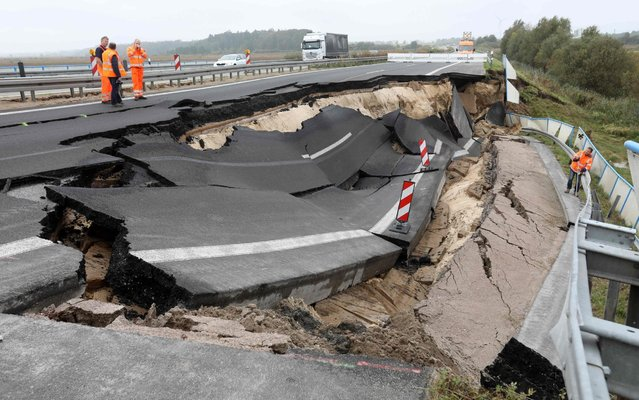 Experts inspect the cut- off section of the A20 motorway at the site of an unexplained landslide near Tribsees, northern Germany, on October 10, 2017. The road to the west slumped about half a meter at the end of September on a length of about 100 meters. Currently, the motorway is completely blocked in the direction of Rostock, in the direction of Stettin is still a trail passable. (Photo by Bernd Wüstneck/AFP Photo/DPA)