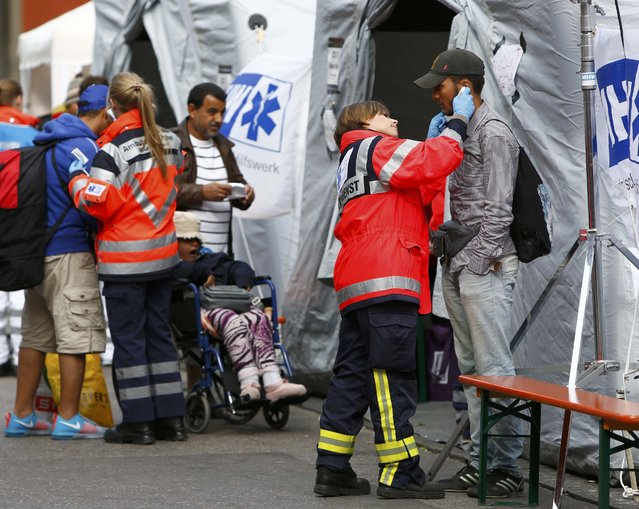 Migrants receive medical checks before boarding buses after arriving by train at the main railway station in Munich, Germany September 7, 2015. About 2,500 refugees are expected to arrive in Germany via Austria by early afternoon on Monday, after an estimated 20,000 came in over the weekend, a Bavarian official told reporters. (Photo by Michaela Rehle/Reuters)