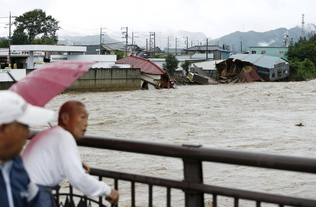 Local residents react as they look at damaged houses and the flooded Kurokawa river, caused by typhoon Etau in Kanuma, Tochigi prefecture, Japan, in this photo taken by Kyodo September 10, 2015. (Photo by Reuters/Kyodo News)