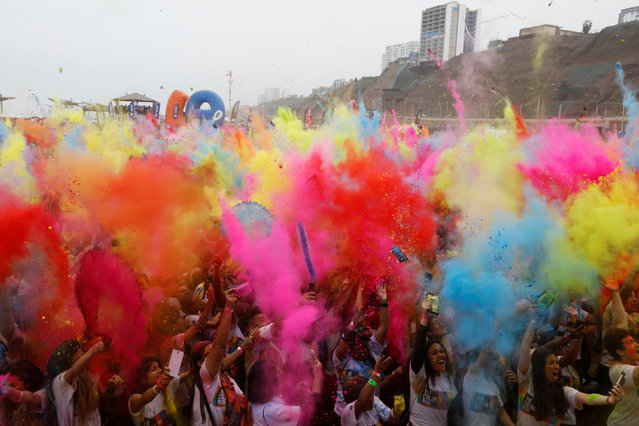 Participants are covered in colored powder as they celebrate in The Color Run in Lima, Peru, August 14, 2016. (Photo by Guadalupe Pardo/Reuters)