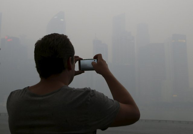 A man takes photos of the skyline of the central business district shrouded by haze in Singapore September 14, 2015. (Photo by Edgar Su/Reuters)