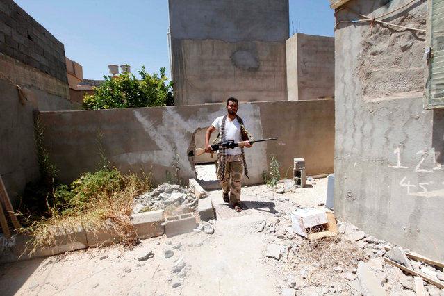 A fighter of Libyan forces allied with the U.N.-backed government holds his weapon as he patrols during a battle with Islamic State fighters in Sirte, Libya August 15, 2016. (Photo by Ismail Zitouny/Reuters)