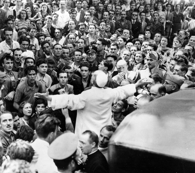 In this October 15, 1943 file photo, men, women and soldiers gather around Pope Pius XII, his arms outstretched, during his inspection tour of Rome, Italy, after the Aug. 13 American air raid during World War II. The Vatican's chief librarian and archivists said Thursday, Feb. 20, 2020 that all researchers – regardless of nationality, faith and ideology – were welcome to request access to the soon-to-open Vatican's apostolic library on Pope Pius XII starting March 2. (Photo by AP Photo/File)