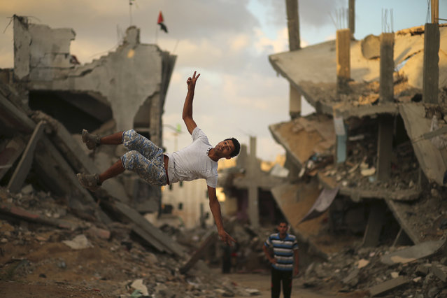 A Palestinian youth practices his Parkour skills near the ruins of houses, which witnesses said were destroyed during a seven-week Israeli offensive, in the Shejaia neighborhood east of Gaza City October 1, 2014. (Photo by Mohammed Salem/Reuters)