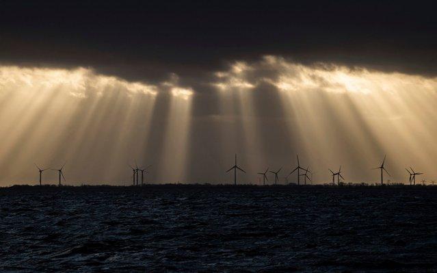 Sunlight breaks through dark clouds illuminating a wind farm in Wilhelmshaven, on the North Sea coast of Germany, the evening of Sunday December 15, 2019. (Photo by Mohssen Assanimoghaddam/dpa via AP Photo)