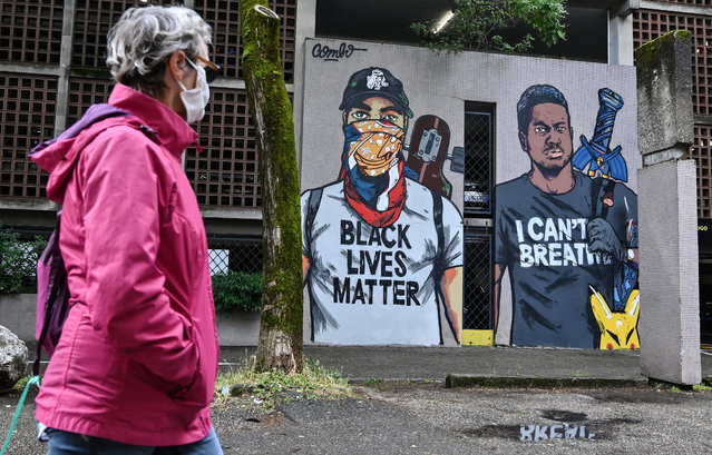 A woman wearing a face mask walks past a mural painted by French artist Combo in homage to George Floyd, an unarmed black man who died after a white policeman knelt on his neck during an arrest in the US, on June 5, 2020, in Grenoble, as part of the 6th Street Art Fest Grenoble-Alpes. (Photo by Philippe Desmazes/AFP Photo)