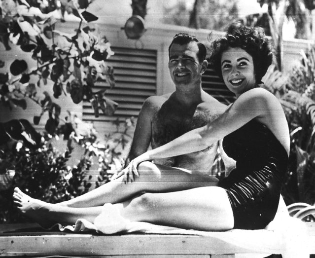 17-year-old British actress Elizabeth Taylor poses with finance William D. Pawley Jr., aged 28, beside the swimming pool at his father's home in Miami beach, Fl., June. 7, 1949.  Mrs Francis Taylor, mother of the young actress, announced the couple's engagement. (Photo by AP Photo)