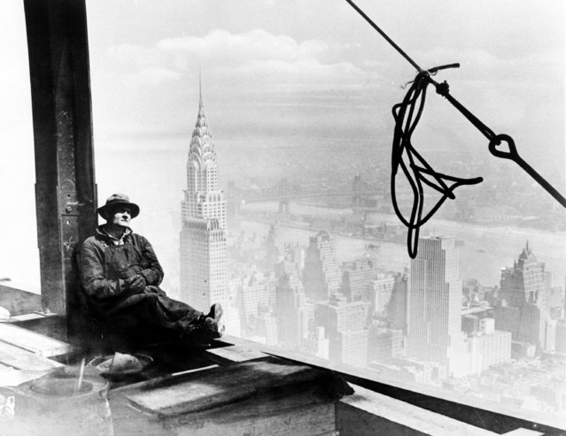A steel worker rests on a girder at the 86th floor of the new Empire State Building during construction in New York City, September 24, 1930. The tower of the Chrysler Building can be seen in background, left. (Photo by AP Photo)