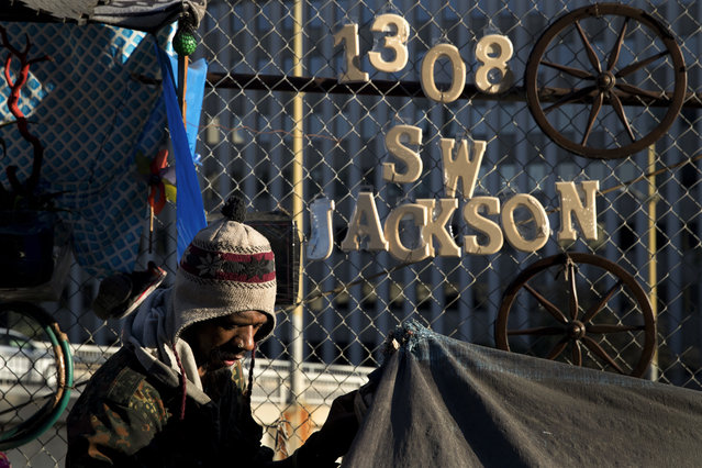 "Thaddeus Bell, 50, who is homeless, sits outside his tent with the street address of his childhood home in Oklahoma hanging on a fence Monday, December 4, 2017, in Los Angeles. ""I might be homeless but I'm human just like everybody else"", said Bell. ""I deserve a real house like any other person"". (Photo by Jae C. Hong/AP Photo)"