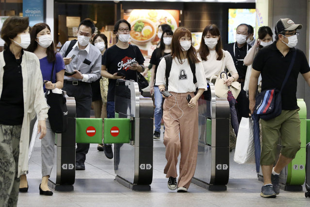 Passengers wearing face masks to protect against the spread of the new coronavirus pass the gates at Yokohama station Tuesday, July 14, 2020. (Photo by Koji Sasahara/AP Photo)