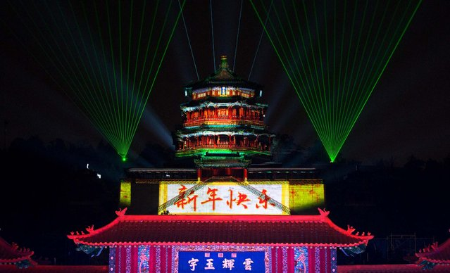 "The pavilion of the Summer Palace is illuminated with lights and the words ""Happy New Year"" during a count-down event in Beijing. (Photo by Andy Wong/Associated Press)"