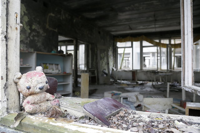 A toy lies in the window frame of a kindergarten in the deserted town of in Pripyat, Ukraine, November 27, 2012, some 3 kilometers (1.86 miles) from the Chernobyl nuclear plant. (Photo by Efrem Lukatsky/AP Photo)