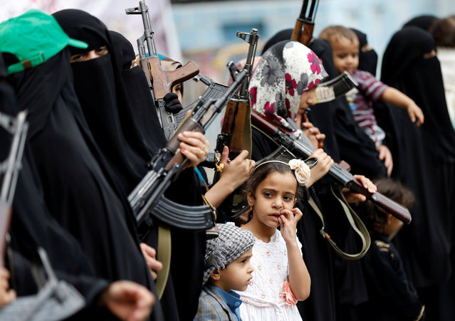 A girl looks at armed women loyal to the Houthi movement as they take part in a parade to show support for the movement in Sanaa, Yemen September 6, 2016. (Photo by Khaled Abdullah/Reuters)