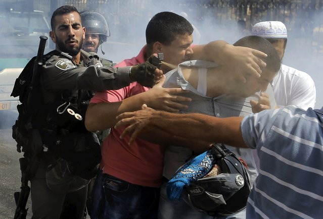 An Israeli border policeman uses pepper spray on a Palestinian man during clashes near the Arab East Jerusalem neighbourhood of Wadi al-Joz October 2, 2015. An Israeli police spokesman said on Friday that Palestinian males under the age of 40 were banned access to al-Aqsa mosque and extra policemen were deployed around the Old City following the deadly shooting of an Israeli couple on Thursday night in the occupied West Bank. (Photo by Ammar Awad/Reuters)